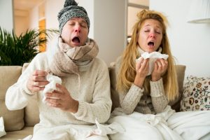 Couple with colds sneezing together.